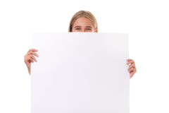 Happy teen girl behind empty board, isolated Royalty Free Stock Photography