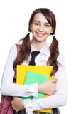 Happy teen girl with books. Happy teen girl holding books and backpack and wide smile Royalty Free Stock Photos