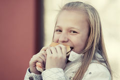 Happy teen girl eating a burger Stock Photography
