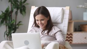 Happy teen girl enjoy using laptop sitting in rocking chair. At home, smiling young woman relaxing with wireless computer having fun online chatting with stock video