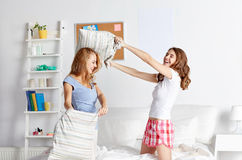 Happy teen girl friends fighting pillows at home Royalty Free Stock Image