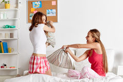 Happy teen girl friends fighting pillows at home Royalty Free Stock Images