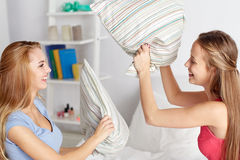 Happy teen girl friends fighting pillows at home Stock Photography