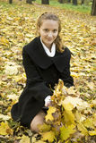 Happy teen girl grabs a bunch of yellow leaves. In autumn park Stock Photos