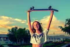 Happy teen girl with her skateboard up in the air, toned image stock photography