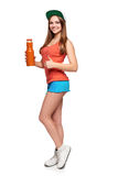 Happy teen girl holding a glass of carrot juice. Healthy eating lifestyle. Happy teen girl holding a bottle of carrot juice and gesturing thumb up standing in stock photography