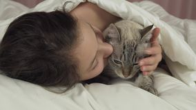 Happy teen girl kisses and talks with Thai cat in bed stock footage video stock video