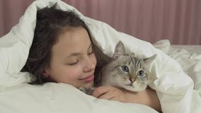 Happy teen girl kisses and talks with Thai cat in bed stock footage video stock footage