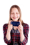 Happy teen girl laughing and use mobile phone. Studio shot Royalty Free Stock Images