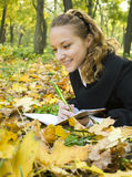 Happy teen girl lies in the park with her diary Stock Photos