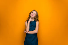 Happy teen girl. The happy teen girl with long hair on orange studio background showing his muscle strength Royalty Free Stock Photo