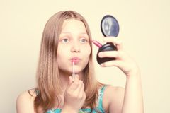 Happy teen girl looking at the mirror. And colors lips Royalty Free Stock Photo