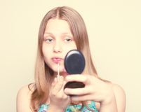 Happy teen girl looking at the mirror. And colors lips Royalty Free Stock Image