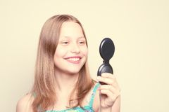Happy teen girl looking at the mirror. And posing Royalty Free Stock Image