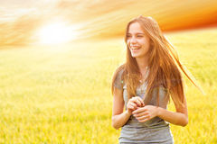 Happy teen girl outside. Beautiful, fit, happy teen girl standing in a field, back lit by a low lying sun Royalty Free Stock Photo