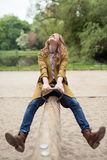 Happy Teen Girl Playing Seesaw at the Park. Happy Blond Teen Girl, Wearing Trendy Outfit, Enjoying her Past Time on Wooden Seesaw at the Park Royalty Free Stock Photos