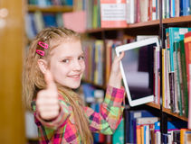 Happy teen girl pulls a tablet pc off the shelves in the library Stock Image