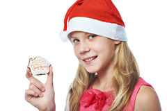 Happy teen girl in red cap with Christmas cookie isolated Royalty Free Stock Photography