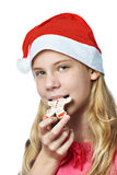 Happy teen girl in red cap eating Christmas cookie isolated Stock Image