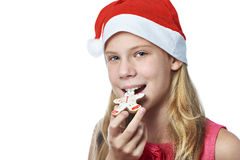 Happy teen girl in red cap eating Christmas cookie isolated Royalty Free Stock Photos