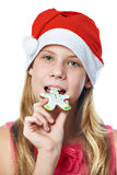 Happy teen girl in red cap eating Christmas cookie isolated Stock Photo
