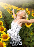 Happy teen girl rejoices in field of sunflowers Royalty Free Stock Photo