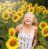 Happy teen girl rejoices in field of sunflowers Royalty Free Stock Photos