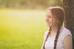 Happy teen girl resting in park under tree Stock Images