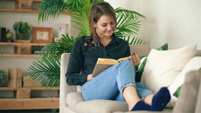 Happy teen girl resting on sofa at the living Room while reading her favorite novel book at home. Indoors stock footage