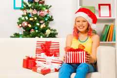 Happy teen girl sitting on the sofa with presents Stock Photo
