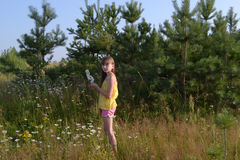 Happy teen girl at summer meadow, collecting flowers royalty free stock image