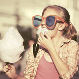 Happy teen girl in sunglasses eating cotton candy in city street Stock Photography