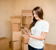 Happy teen girl with tablet computer standing on a background of boxes.  Stock Photo