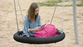 Teen girl on swing. Happy teen girl with tablet pc and backpack on swing in playground outdoors. Beautiful student teenager using gadget. Child having fun after stock video