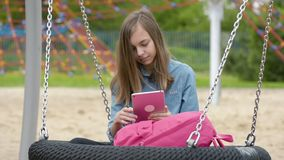 Teen girl on swing. Happy teen girl with tablet pc and backpack on swing in playground outdoors. Beautiful student teenager using gadget. Child having fun after stock footage