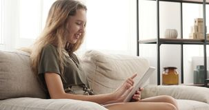 Happy teen girl using digital tablet on sofa stock video footage