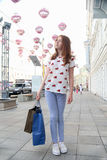 Happy teen girl walking down the street. Of the city happy after successful shopping and listening to music Stock Photos