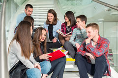 Happy teen girls and boys on the stairs school or college Stock Photos