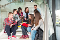 Happy teen girls and boys on the stairs school or college. Selective focus Royalty Free Stock Photos