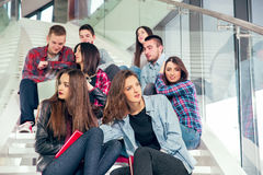Happy teen girls and boys on the stairs school or college Royalty Free Stock Images