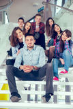 Happy teen girls and boys on the stairs school or college. Selective focus Royalty Free Stock Photography
