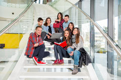 Happy teen girls and boys on the stairs school or college Stock Image