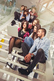 Happy teen girls and boys on the stairs school or college. Selective focus Stock Image