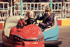 Happy teen girls driving a bumper cars Stock Images