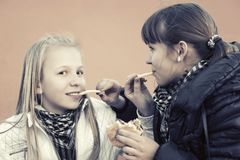 Happy teen girls eating a burgers and french frees Royalty Free Stock Images