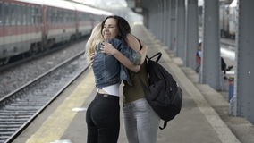 Happy teen girls reunited in train station hugging and walking home hand in hand. Two happy teen girls reunited in train station hugging and walking home hand in stock video
