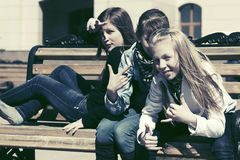 Happy teen girls sitting on bench in a city street Royalty Free Stock Photo