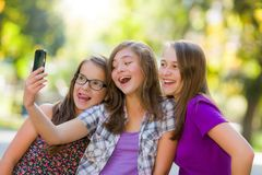 Happy teen girls taking selfie in park Stock Photos
