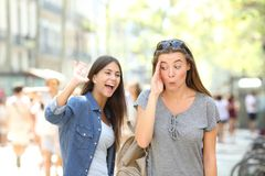 Teen greeting and friend ignoring her in the street. Happy teen greeting waving hand and friend ignoring her in the street Royalty Free Stock Photography