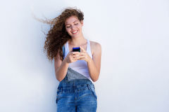 Happy teen holding cellphone and smiling with hair blowing Royalty Free Stock Photos